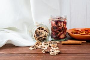 Dried fruits in glass jars on a wooden background