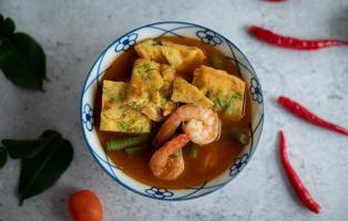 Hot and sour soup with cha-om, egg, and shrimp photo