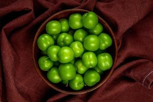 Top view of green sour plums in a wooden bowl on a dark red fabric photo