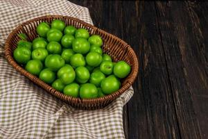 Green sour plums in a wicker basket on checked fabric photo