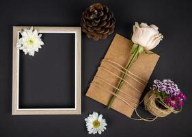 Top view of an empty picture frame with a card and flowers on a black background