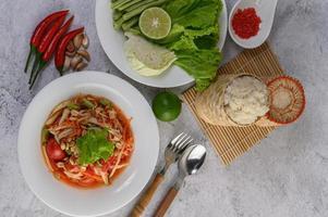 ensalada tailandesa de papaya en un plato blanco con arroz glutinoso, cuchara, tenedor y camarones secos. foto