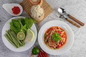 ensalada tailandesa de papaya con arroz glutinoso, lima y chile foto
