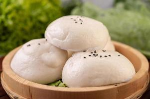 Steamed buns in a wooden dish