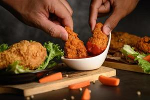 Two hands holding crispy chicken tenders in tomato sauce photo