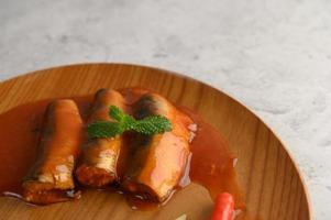 Sardinas en salsa de tomate en una bandeja de madera foto