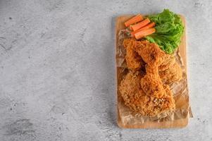 Pollo frito crujiente sobre una tabla para cortar foto