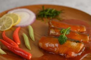 Sardinas en salsa de tomate en bandeja de madera foto