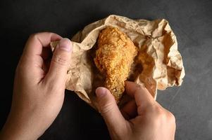Hands picking up crispy fried chicken on brown paper
