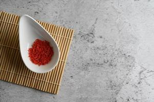 Small red dried shrimp in a cup on a wooden mat photo
