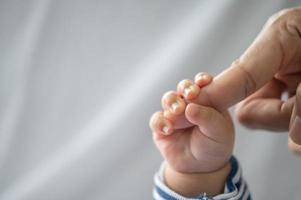 The hand of the newborn baby holding the fingers of the mother