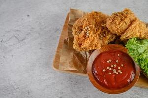 Pollo frito crujiente sobre una tabla de cortar con salsa de tomate, vista superior foto