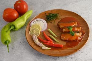 Ensalada de sardina picante en una placa de madera foto