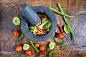 cocinar comida tailandesa, ensalada de papaya y condimentos en una mesa de madera