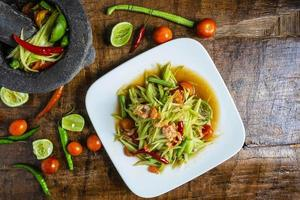 Papaya salad on a white plate on a wooden table