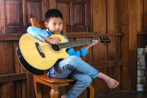 Boy playing an acoustic guitar photo