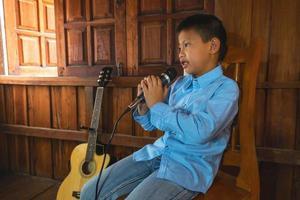 niño cantando junto a una guitarra