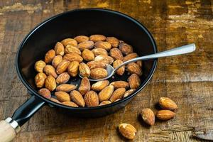 Almonds in a pan with a spoon photo