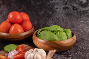 tomillo y tomates en una taza de madera con ajo