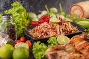 Thai papaya salad surrounded by vegetables and chicken