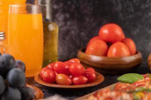 tomates frescos, uvas y jugo de naranja en un vaso