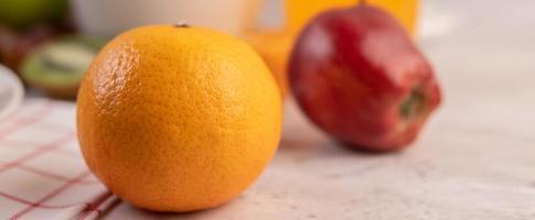 una naranja y una manzana roja foto