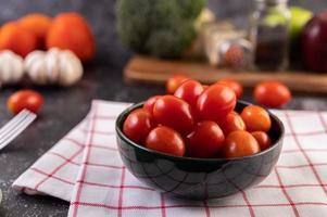 Tomates maduros frescos sobre una tela escocesa roja