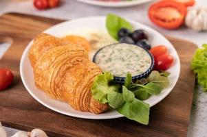 croissant, huevo frito, aderezo para ensaladas, uvas negras y tomates