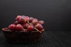 Uvas rojas sobre un fondo de madera oscura.