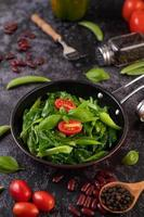 Sauteed kale in sauce pan with tomatoes, peppers and beans layout photo