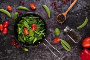 Sauteed kale in sauce pan with tomatoes