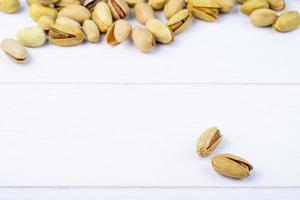 Pistachios on white wooden background with copy space
