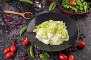 Stir fried cabbage on a black plate with tomatoes photo