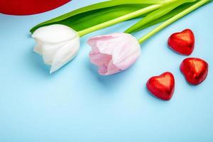 Tulips and heart-shaped candies on a blue background