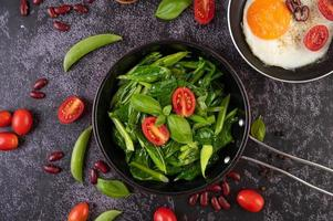 Sauteed kale in sauce pan with tomatoes, peppers and beans