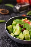 Cucumbers with tomatoes in a frying sauce pan