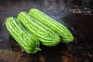 Green gourds on a dark wooden table photo