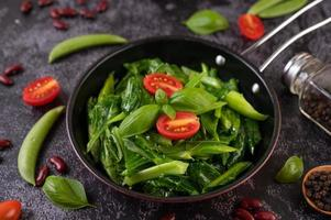 Stir-fried kale in a pan with tomatoes and peppers
