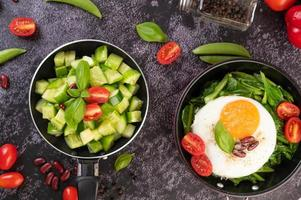 Cucumbers with tomatoes and egg in a frying pan photo