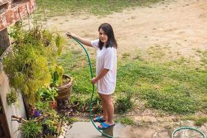 mujer regando plantas en un patio