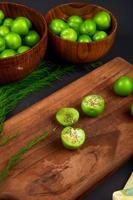 Green plums sprinkled with dried peppermint on a wooden cutting board