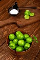 Sour green plums in a wooden bowl and a cutting board photo