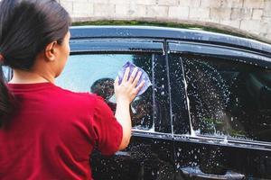 Close-up of a woman washing a car photo