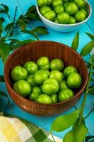 Bowls of sour green plums photo