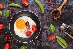 Fried egg in a frying pan with tomato