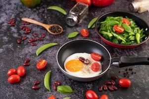 Fried eggs in a frying pan with tomato