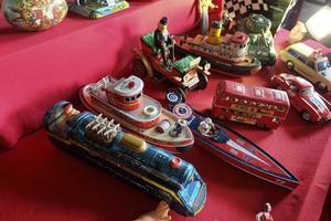 Juguetes de vehículos de hojalata antiguos en bazar de antigüedades