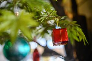 Close-up of a gift box ornament hanging from the Christmas tree
