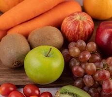 lose-up of apples, grapes, carrots and oranges together photo