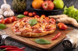 Pizza casera en bandeja de madera con tomate, ají y albahaca foto